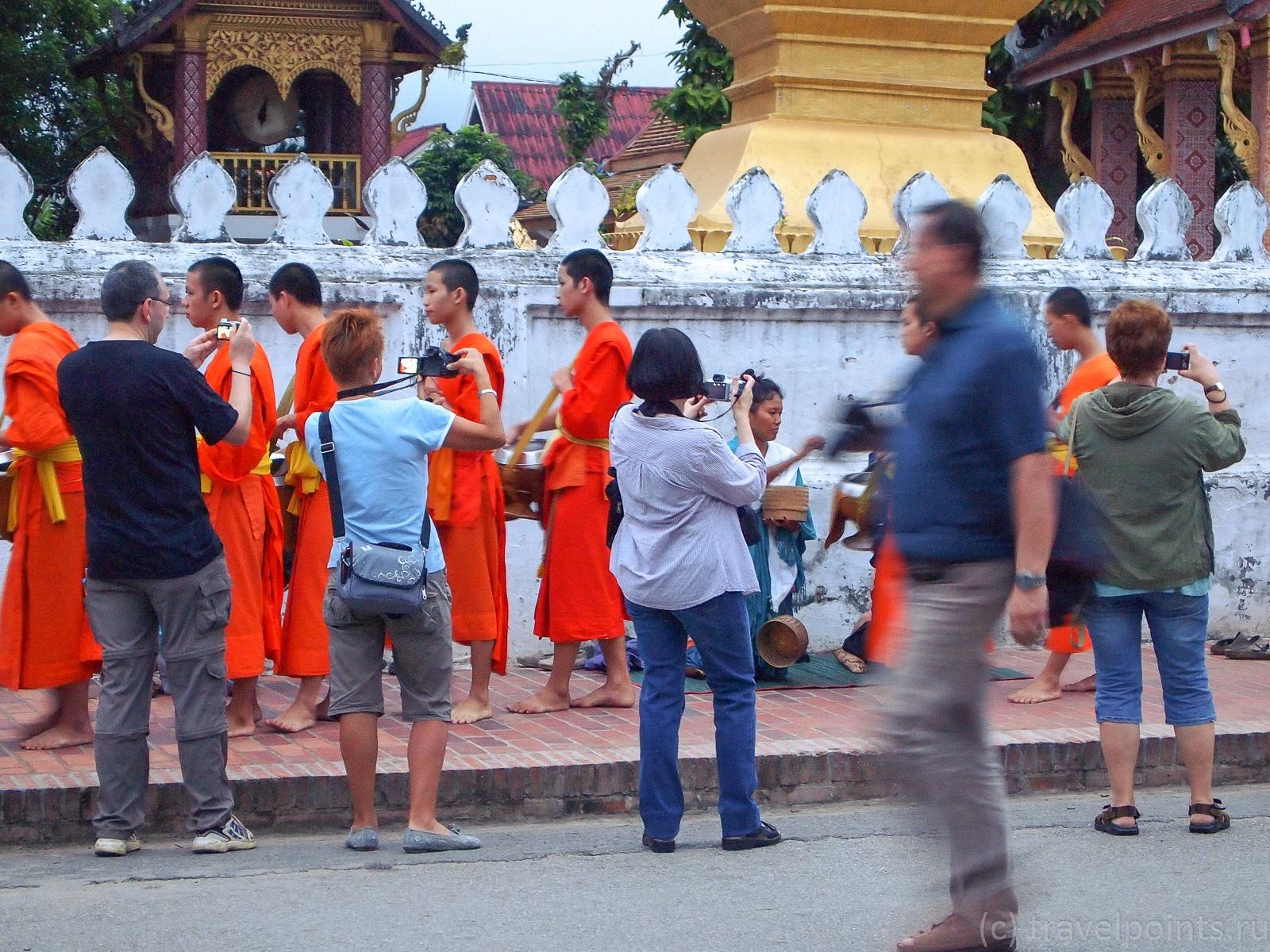 Туристы, фотографирующие монахов
